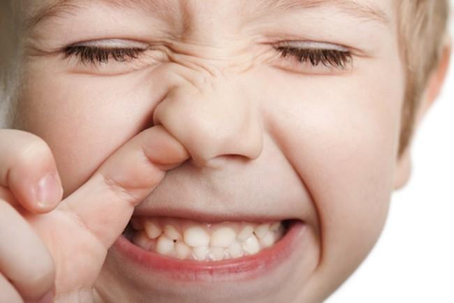 criança com dedo no nariz